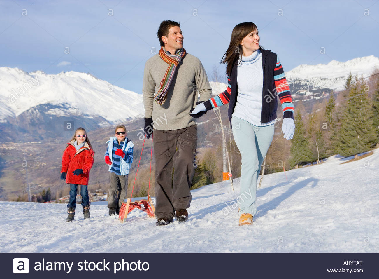 Young couple pulling sled in snow field in front of daughter and son , mountain range in background - Stock Image