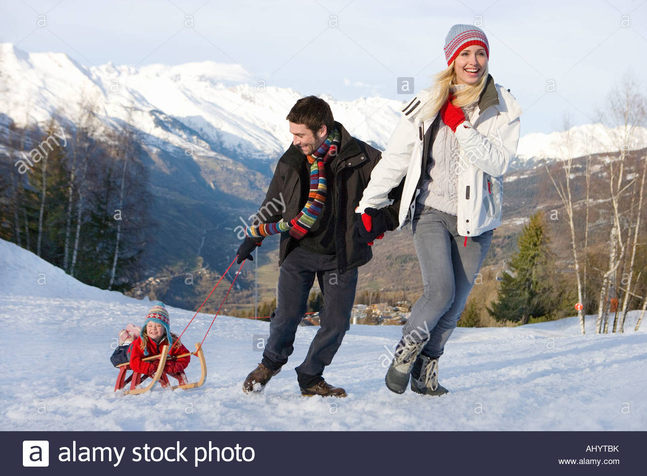 Young couple pulling daughter  on sled in snow field, smiling, mountain range in background - Stock Image