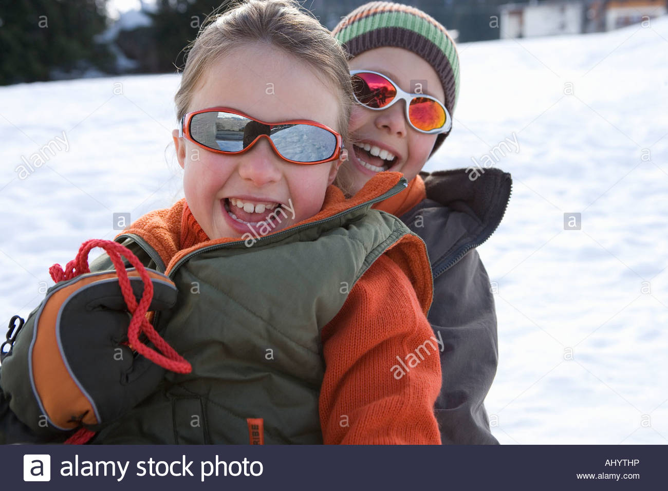Boy and girl  on sled in snow, wearing sunglasses, smiling, portrait Stock Photo
