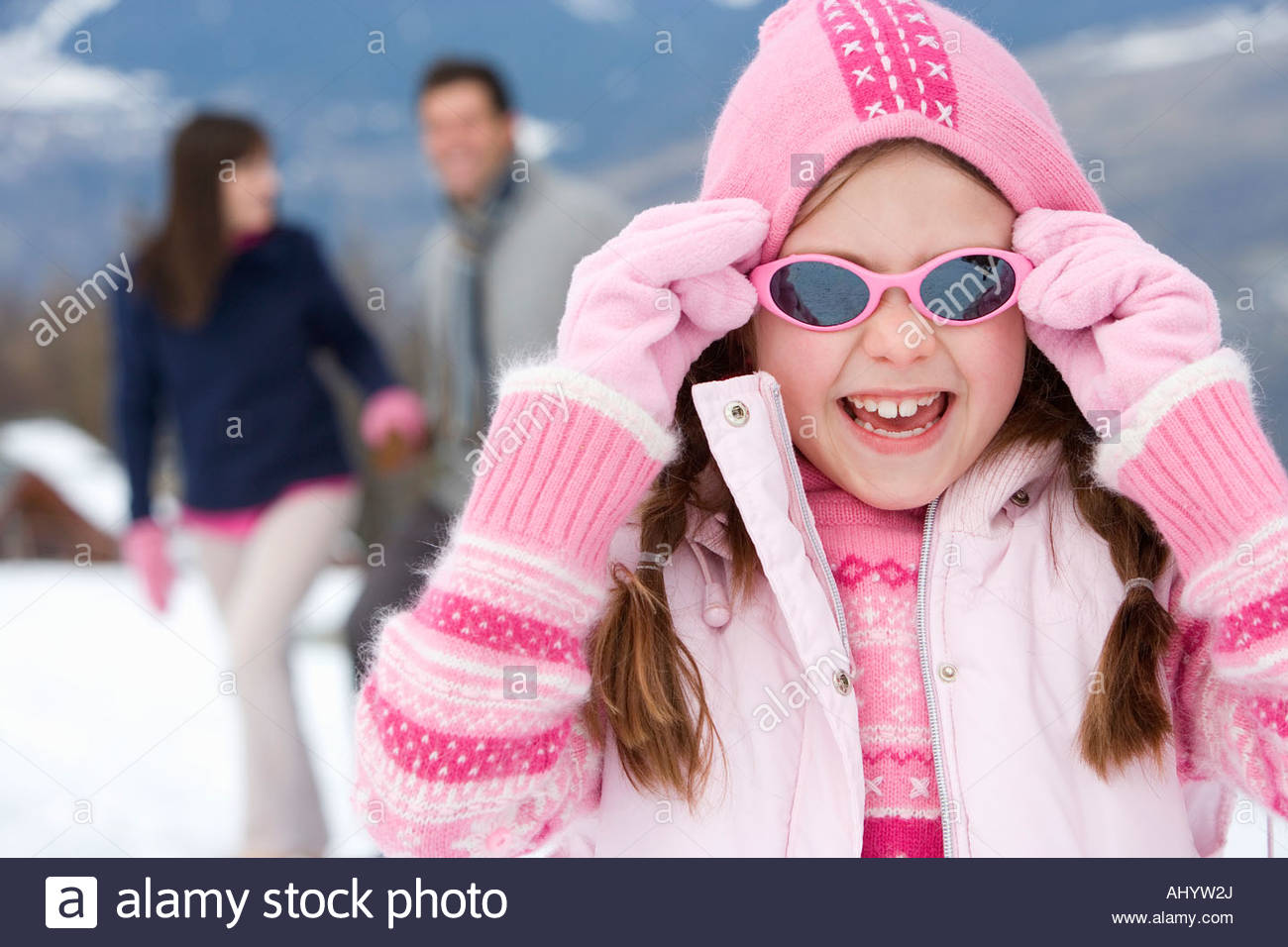 Girl  wearing woolen hat and sunglasses in snow, smiling, portrait, parents in background Stock Photo