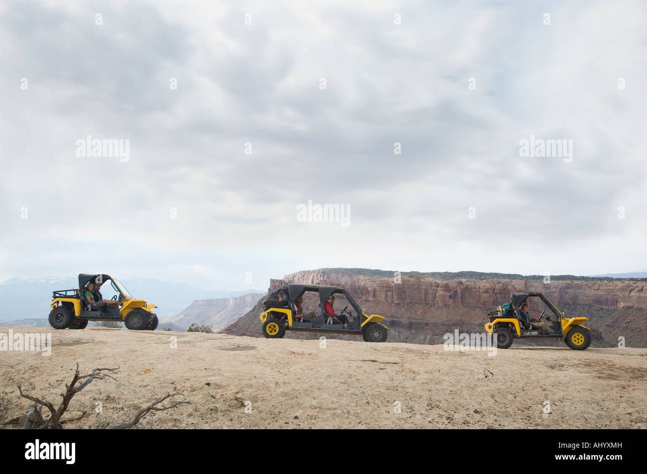 People in off-road vehicles on rock formation - Stock Image