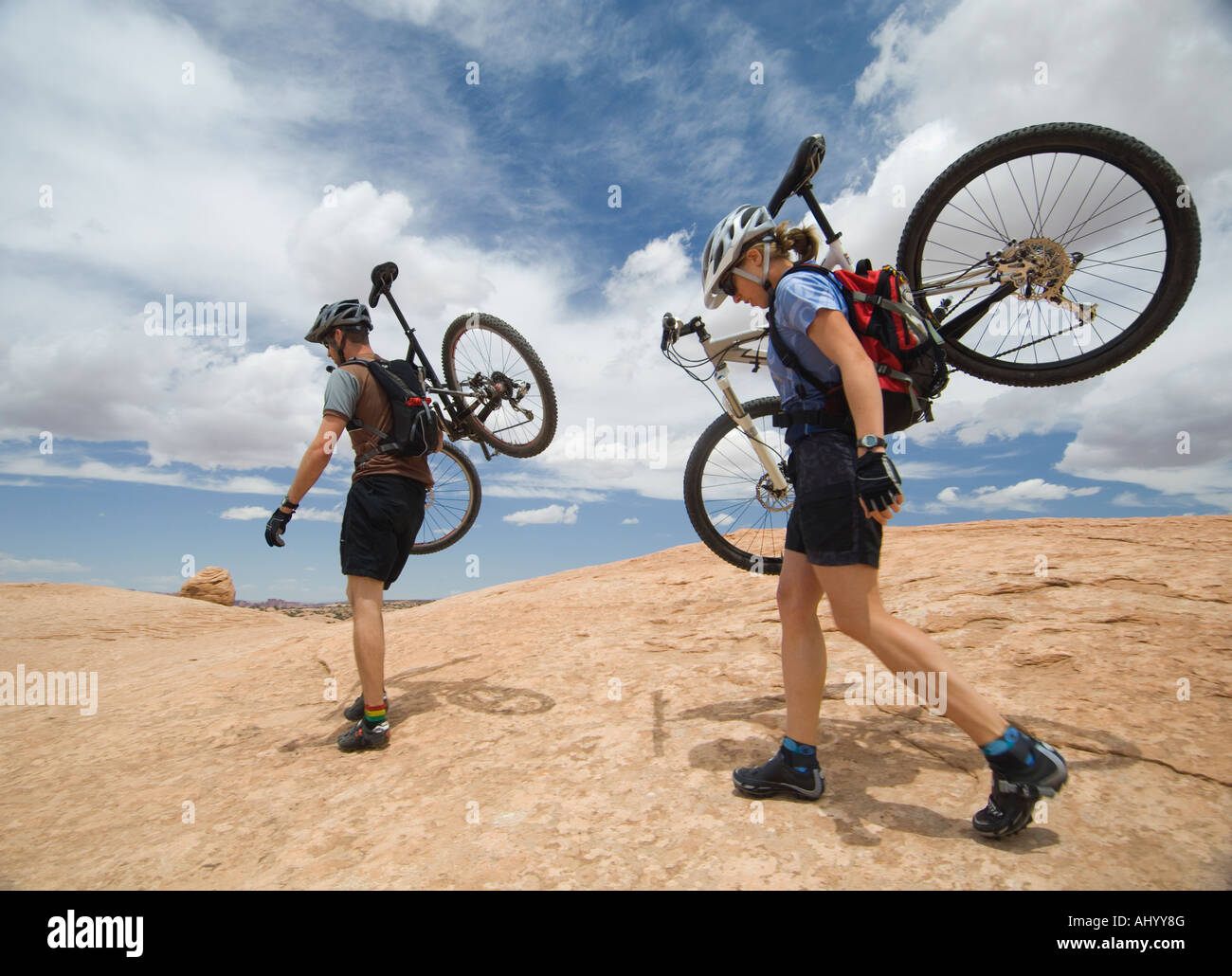 Couple carrying mountains bikes in desert - Stock Image