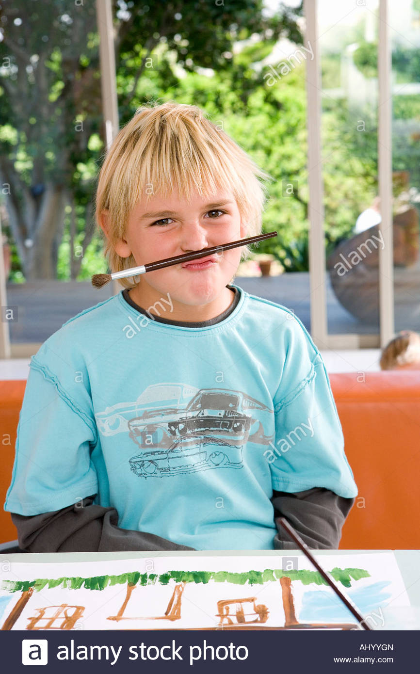 Boy  holding paint brush between nose and mouth, portrait - Stock Image