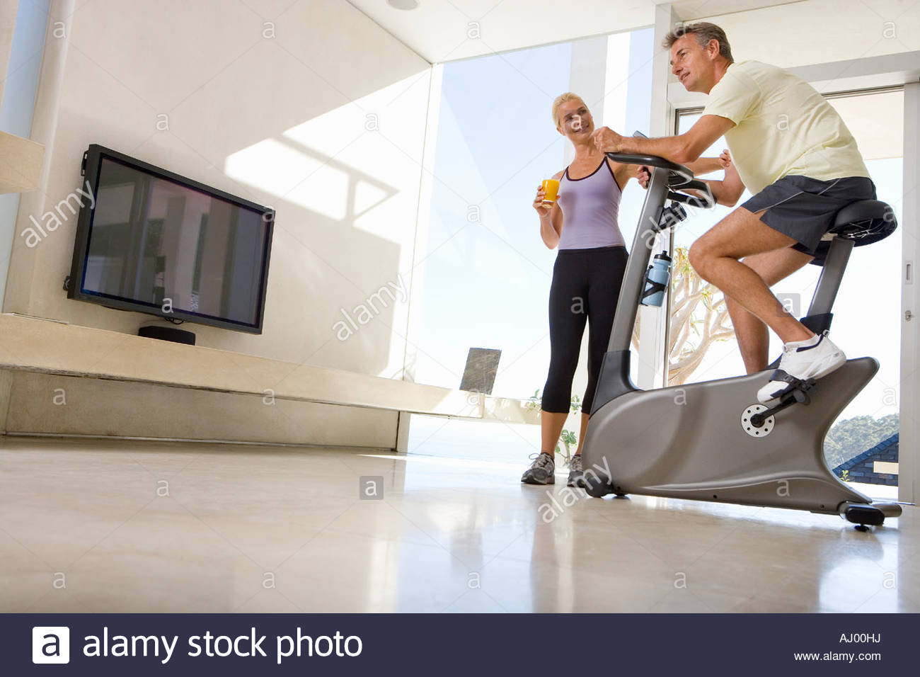 Mature woman smiling at mature man riding stationary bicycle in ...