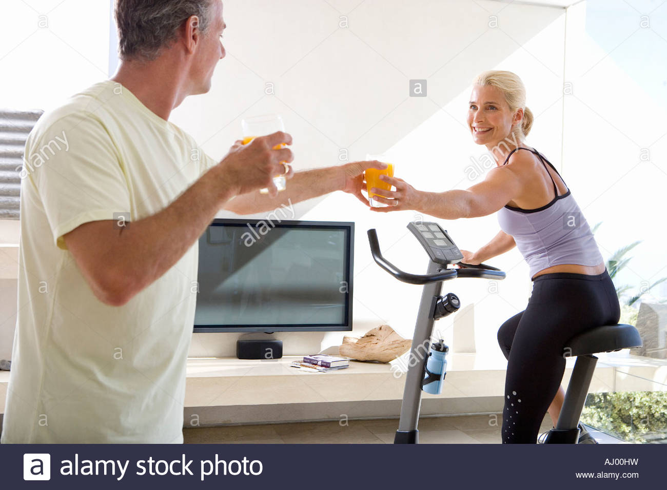 mature man passing glass of juice to mature woman riding stationary