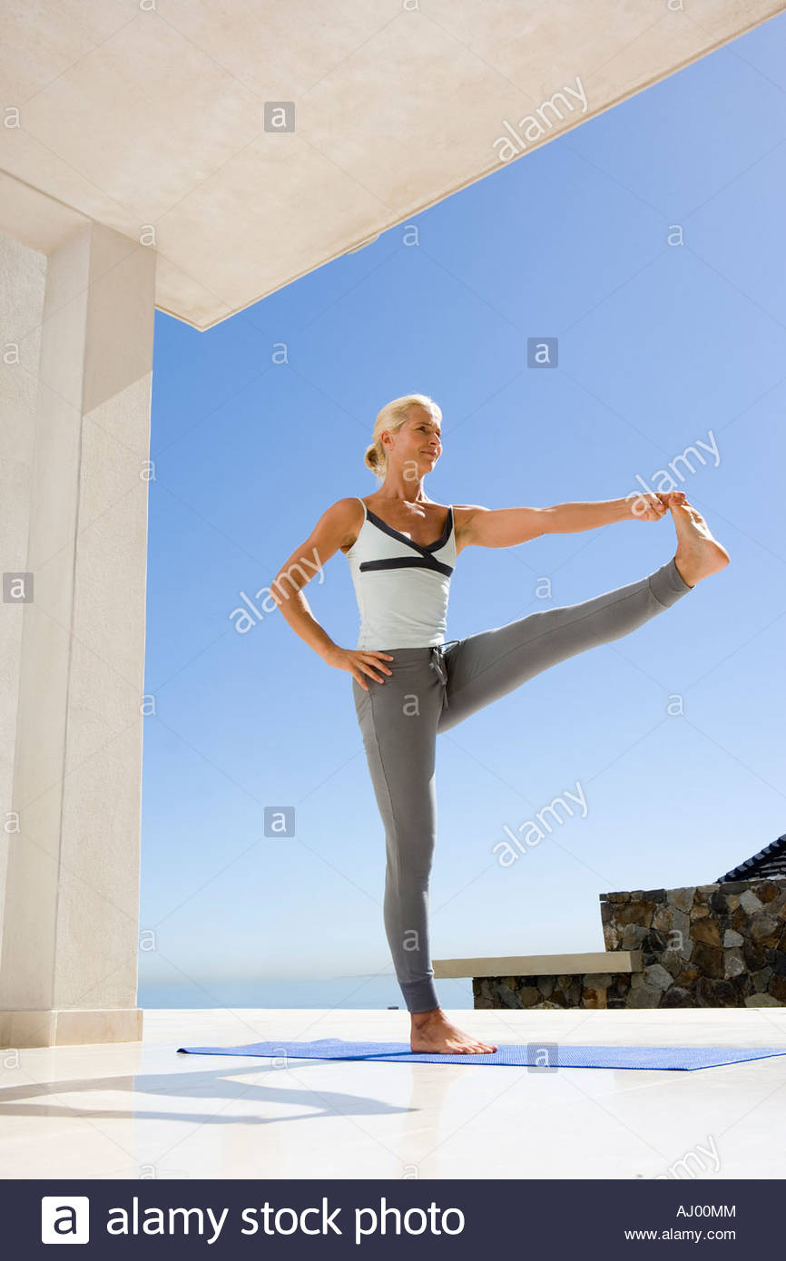Mature woman in standing yoga position on exercise mat outdoors, low angle view - Stock Image