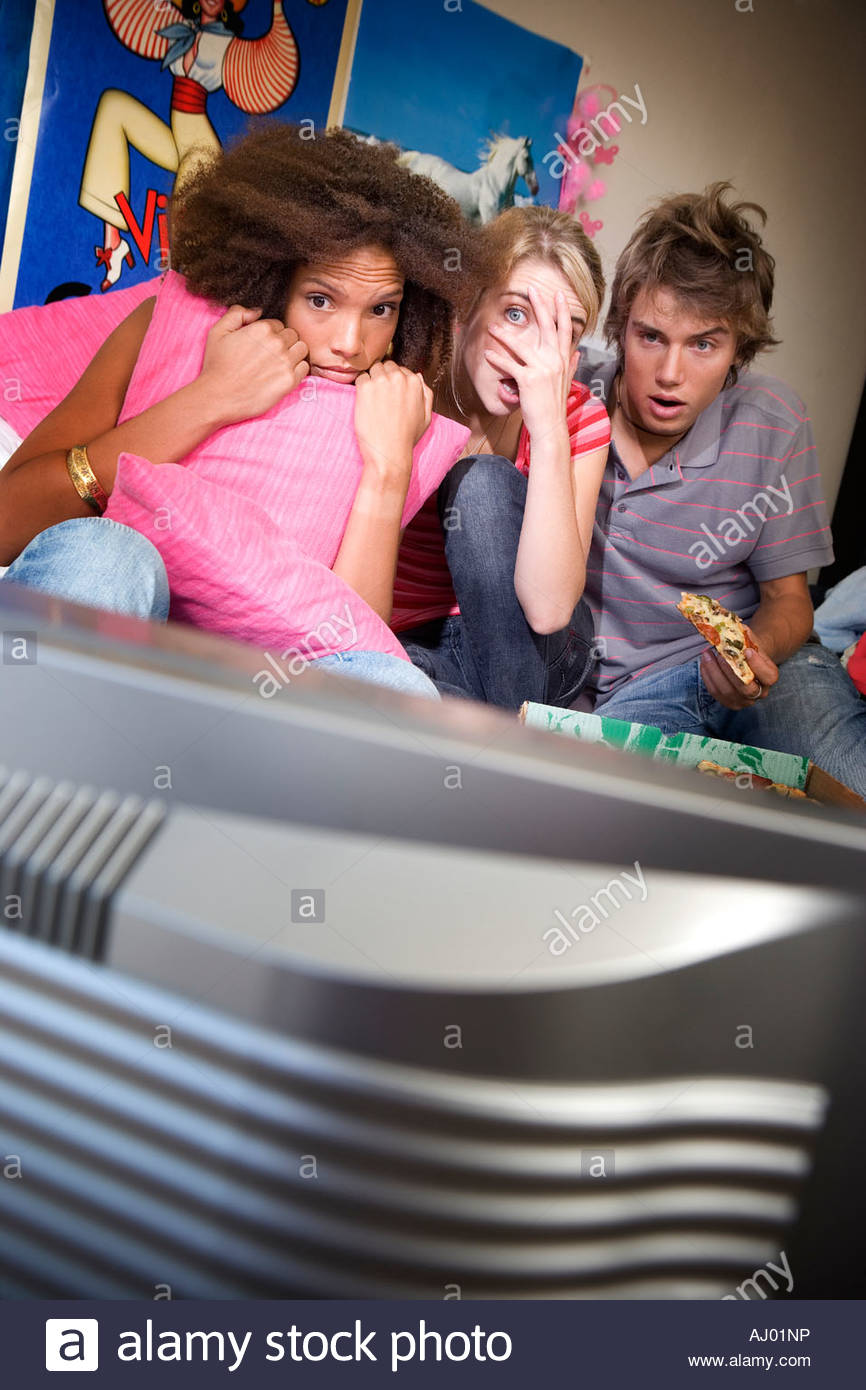 Three teenage friends  watching television with scared expressions on faces, television in foreground - Stock Image