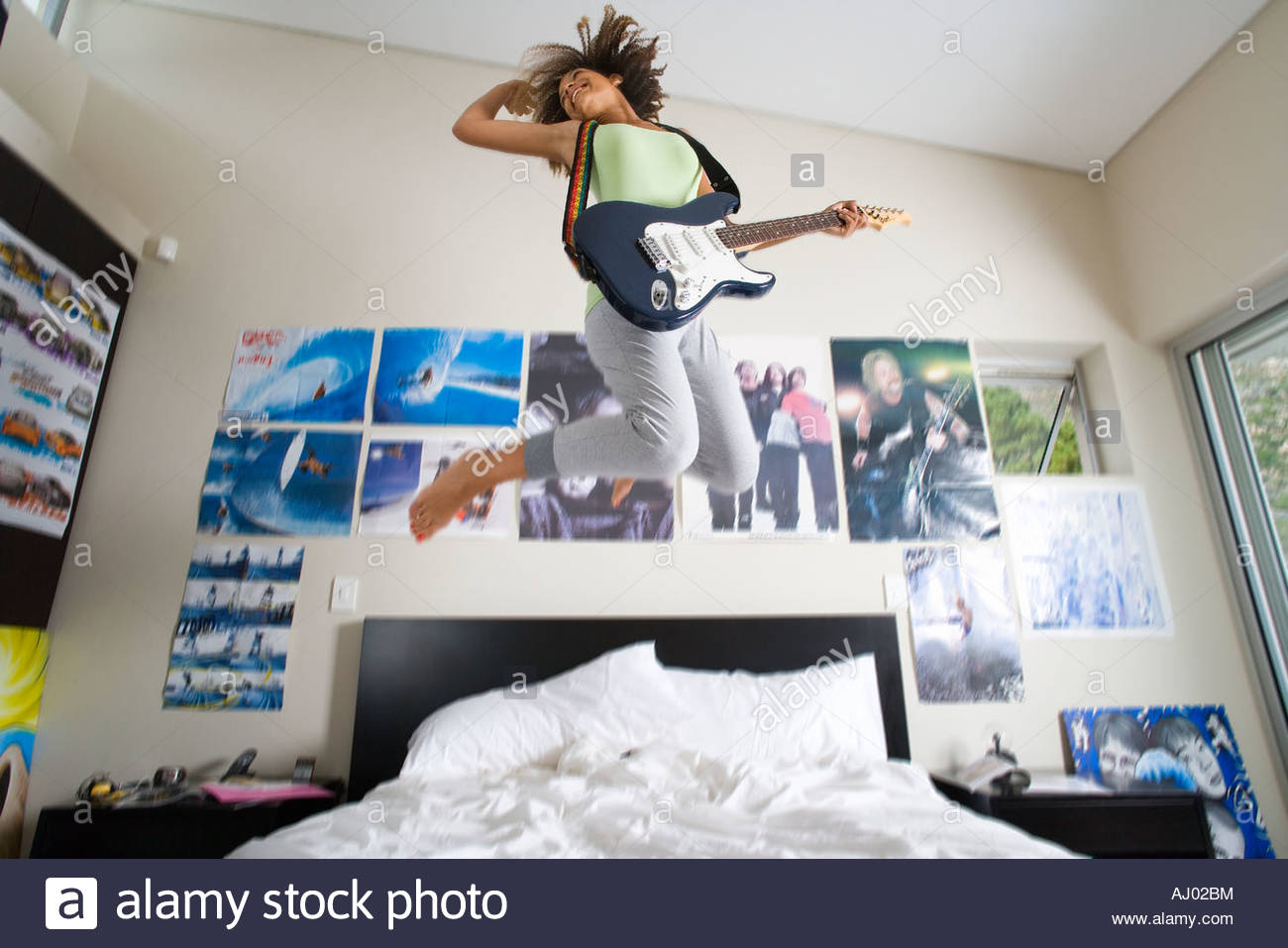 Teenage Girl Playing Electric Guitar Jumping In Air Above Bed Low