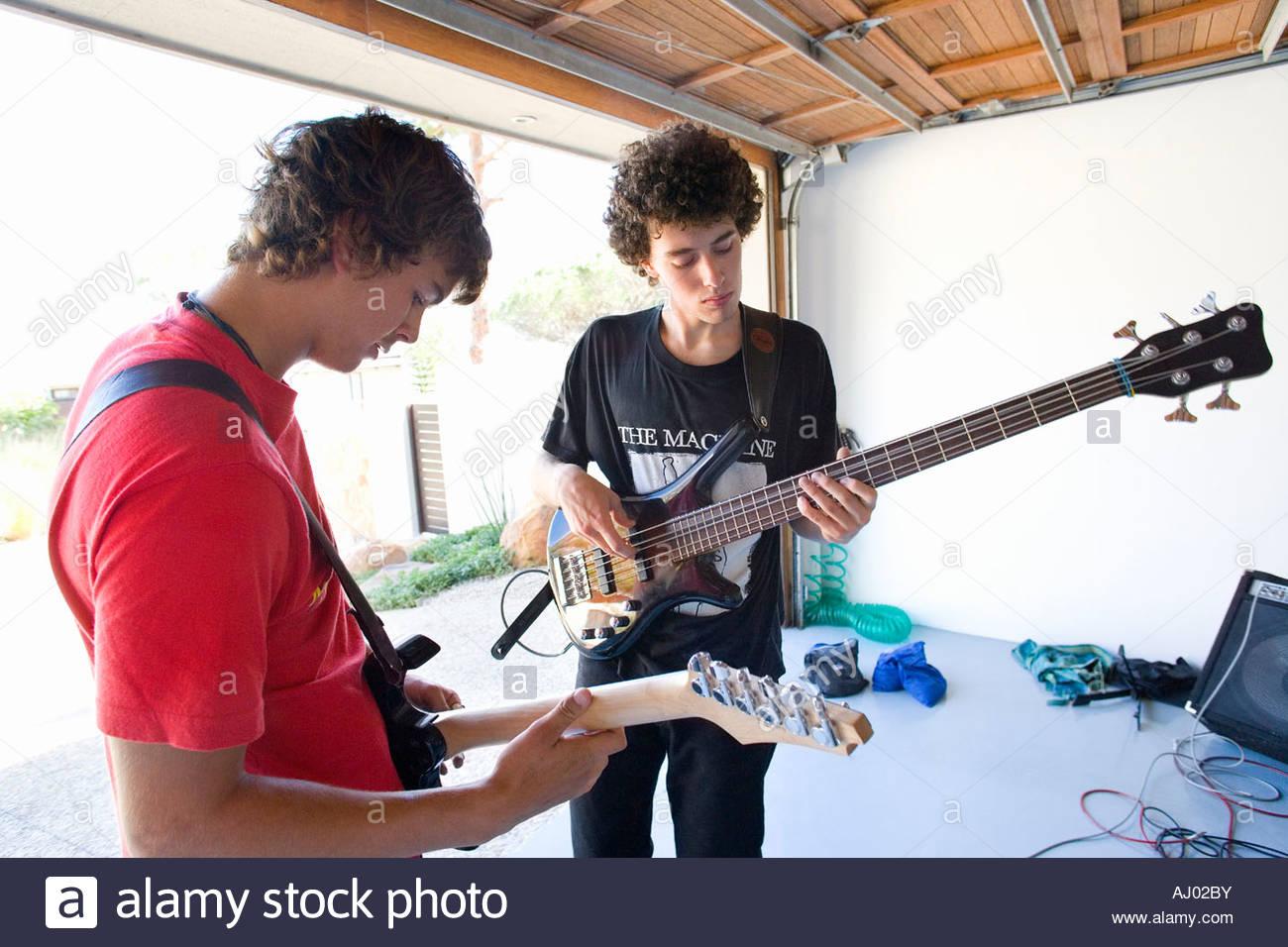 Two teenage boys  playing guitars in garage - Stock Image