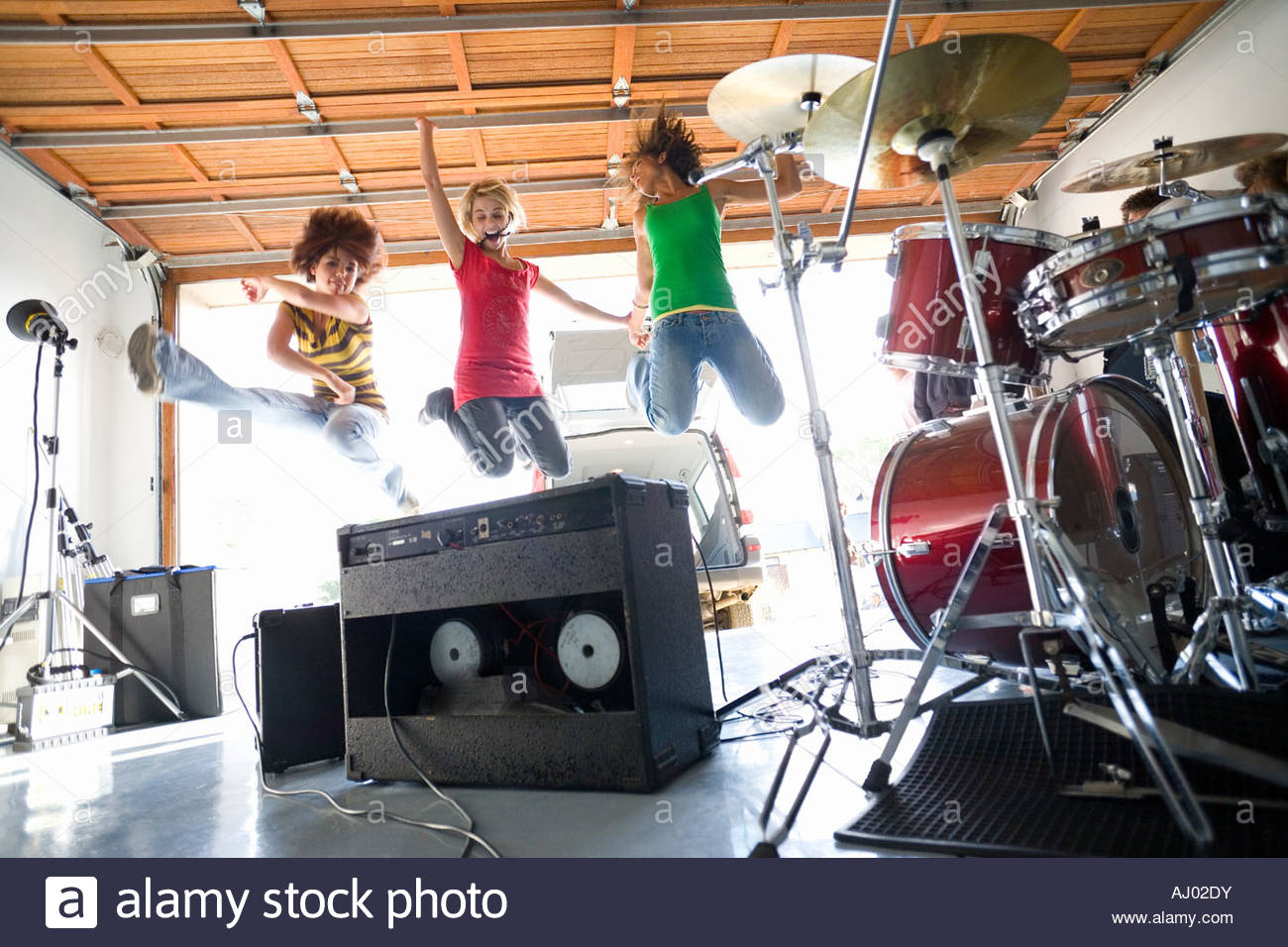 Three teenage girls  jumping in air by drum kit and amplifiers, smiling, low angle view - Stock Image