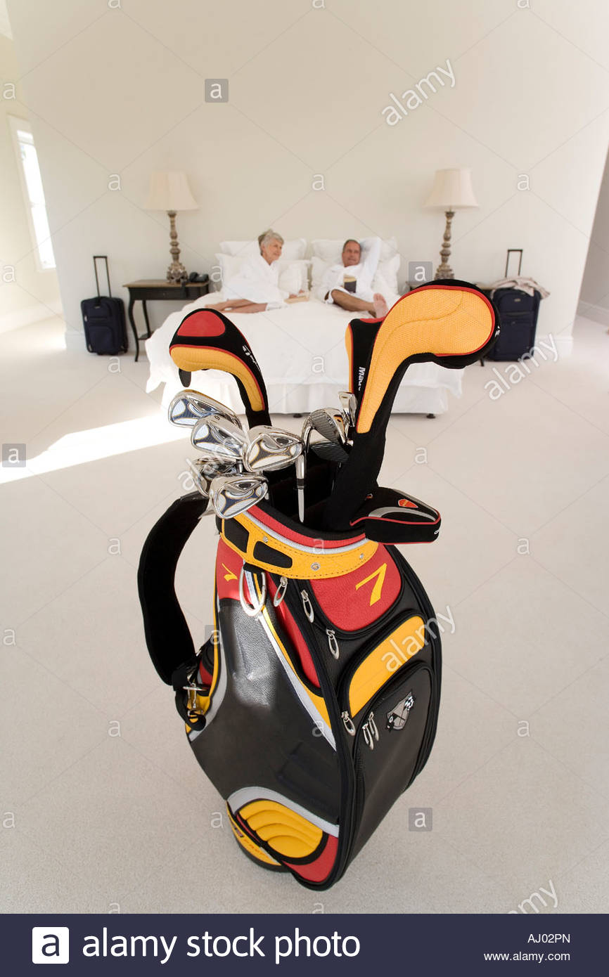 Golf clubs by senior couple lying in bed - Stock Image