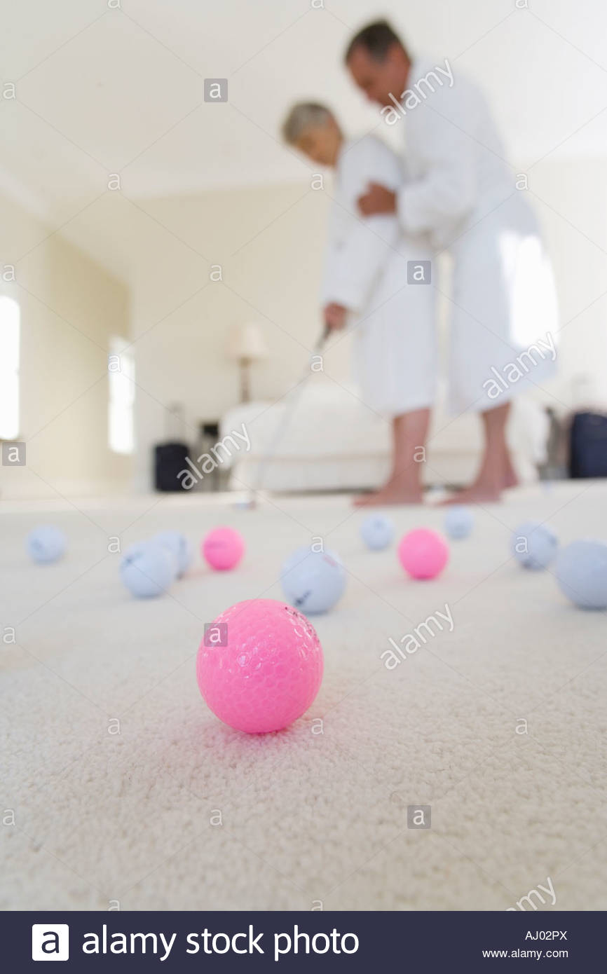 Senior couple in bedroom practising golf putt, focus on golf balls in foreground - Stock Image