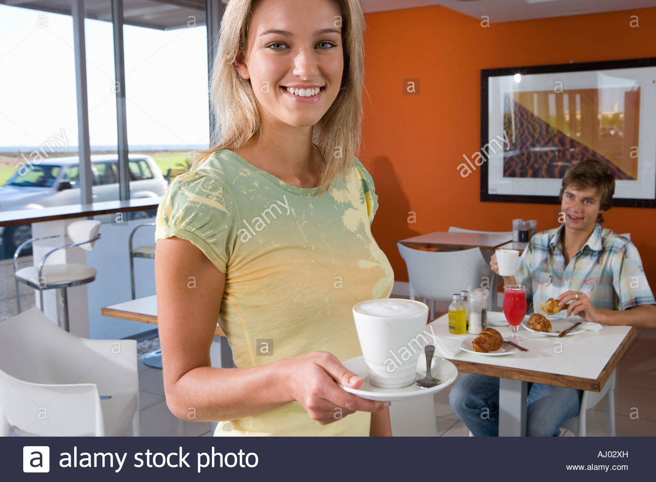 Young woman holding tea cup in cafeteria, smiling, portrait, young man smiling in background - Stock Image