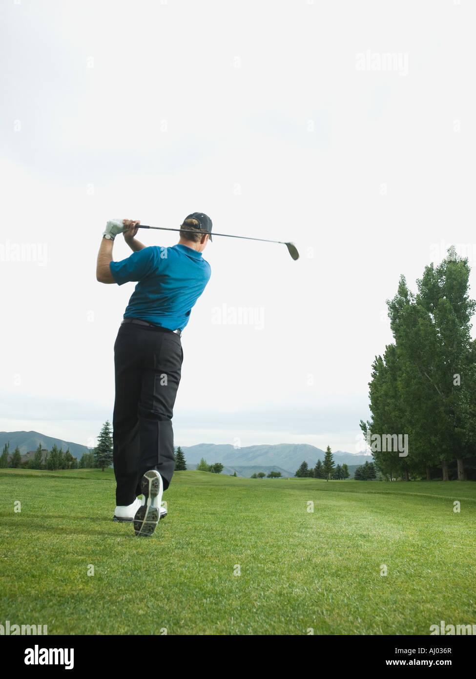 Man swinging golf club - Stock Image