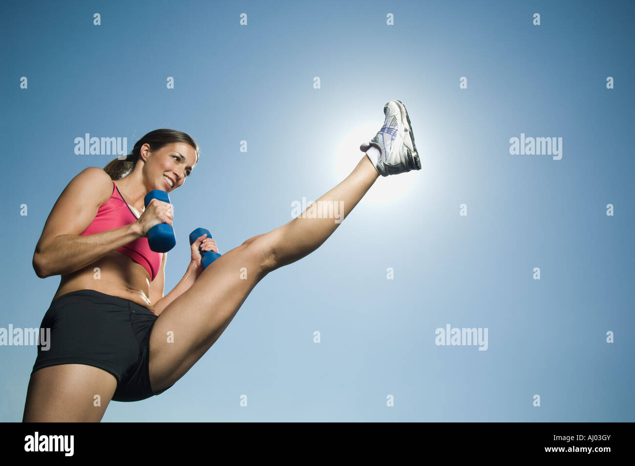 Woman in athletic gear kicking - Stock Image