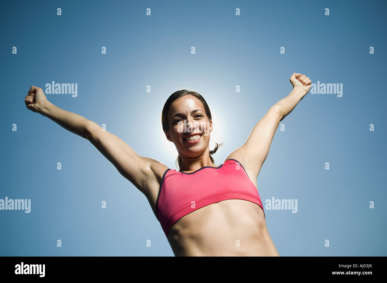 Woman in athletic gear with arms raised - Stock Image