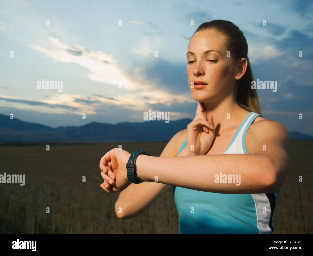 Woman in athletic gear checking pulse - Stock Image