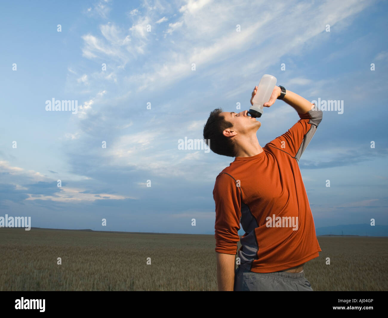 Man in athletic gear drinking water - Stock Image