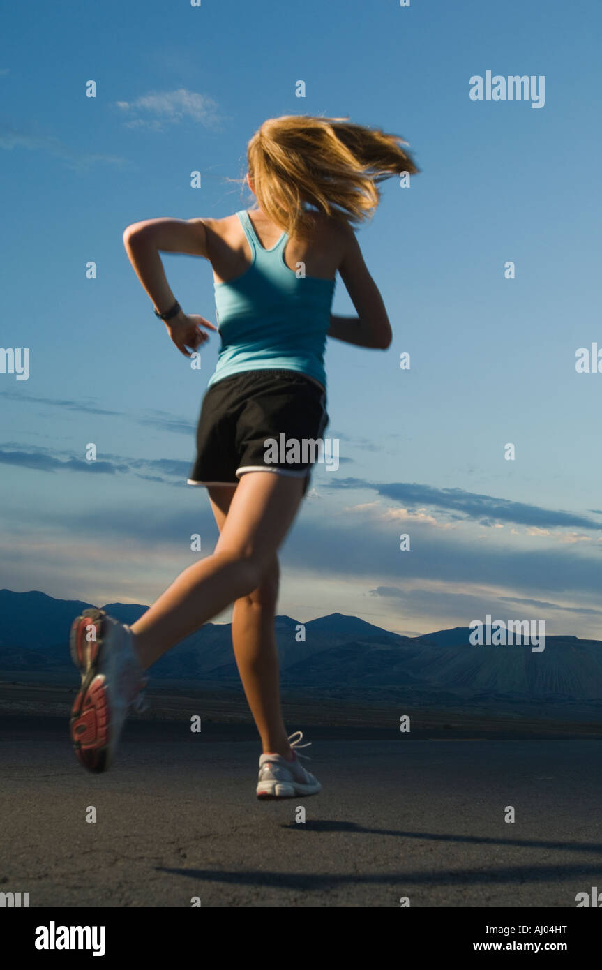 Woman in athletic gear running - Stock Image
