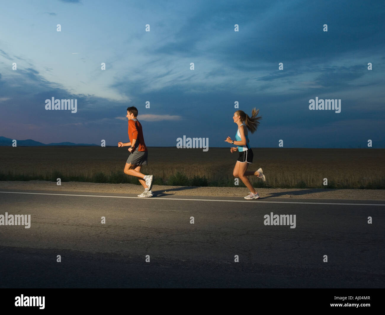Couple in athletic gear running - Stock Image