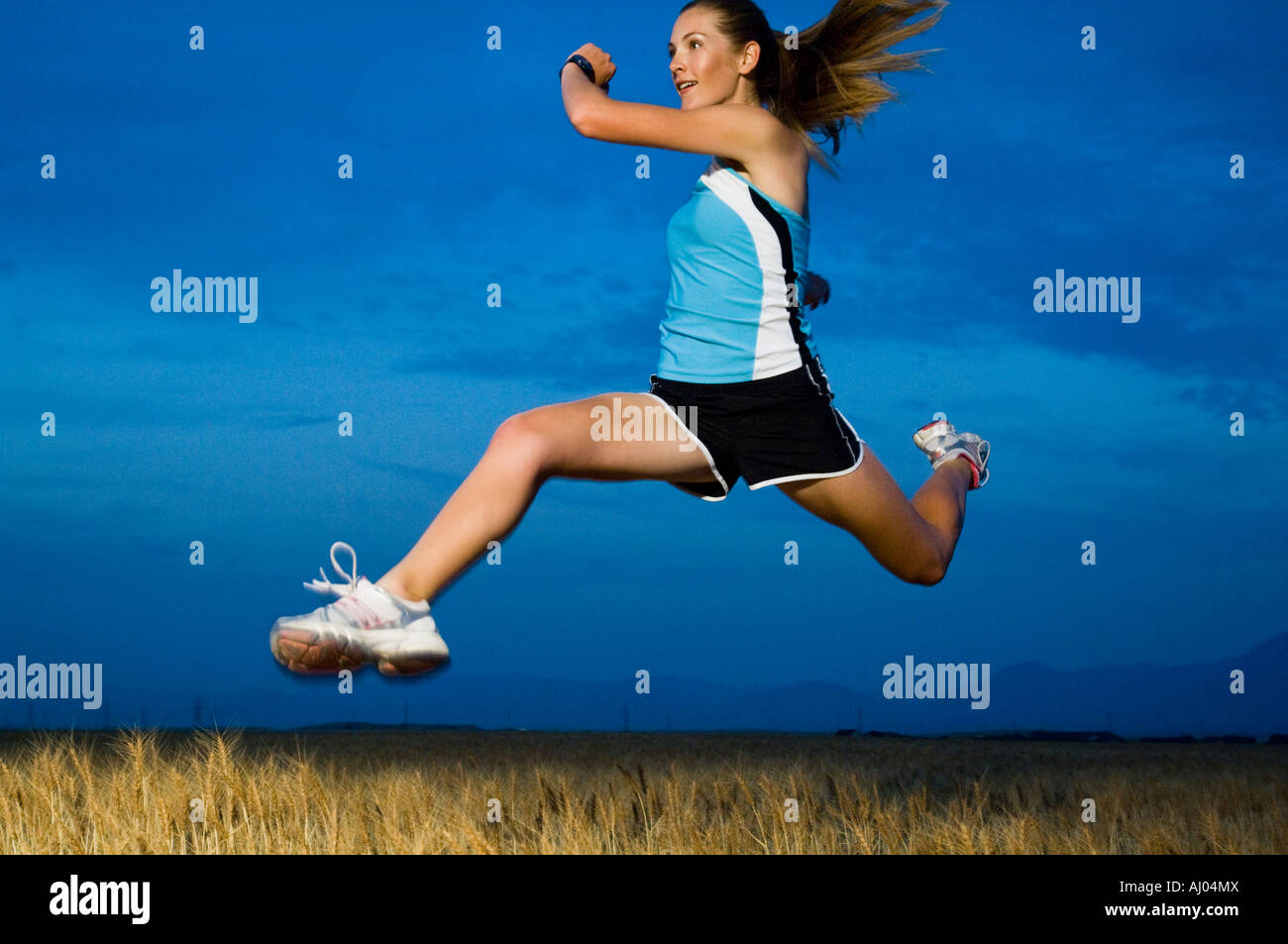 Woman in athletic gear jumping - Stock Image