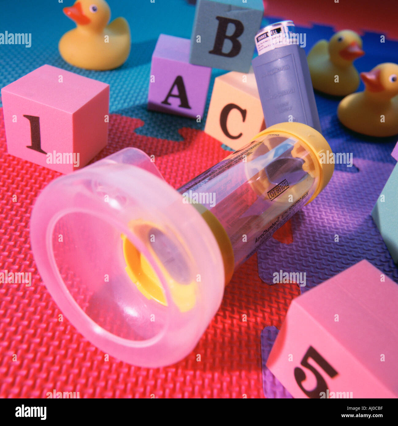 Close up of a child asthma inhaler lying on a puzzle mat amongst alphabet blocks and yellow toy ducks - Stock Image