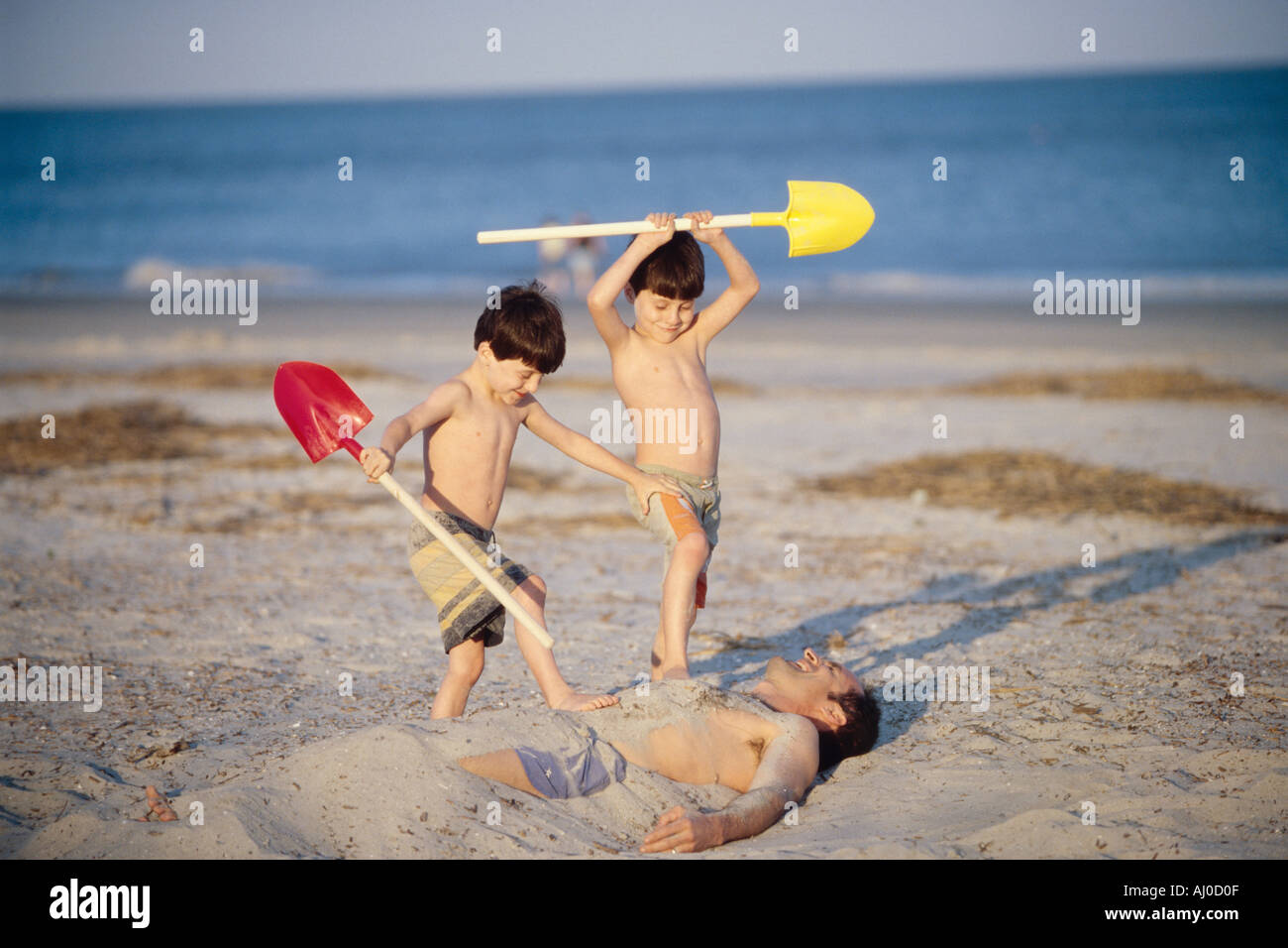 Young twin brothers wield plastic shovels ads they bury their father in the sand at a beach - Stock Image