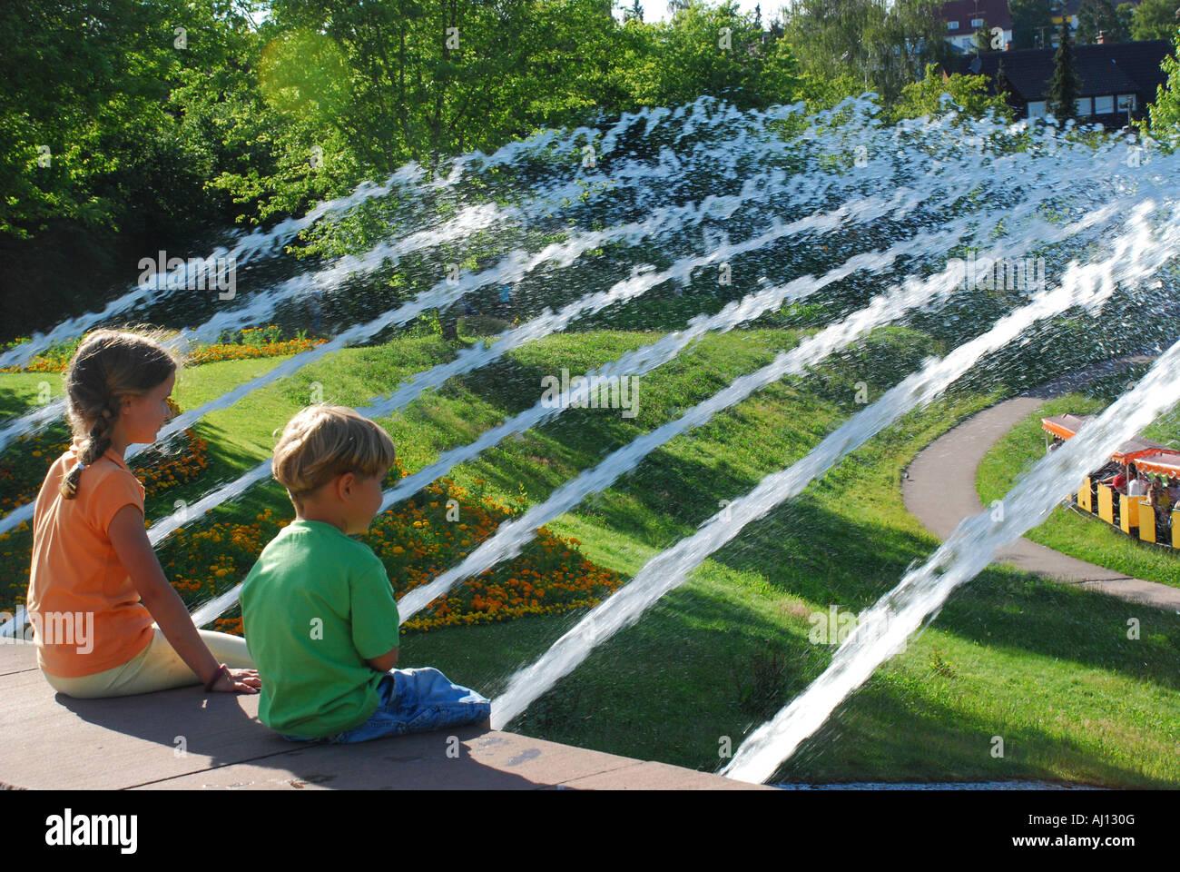 Kinder bestaunen die Kleinbahn Tatzelwurm vor Wasserspielen im Höhenpark Killesberg Stuttgart - Stock Image