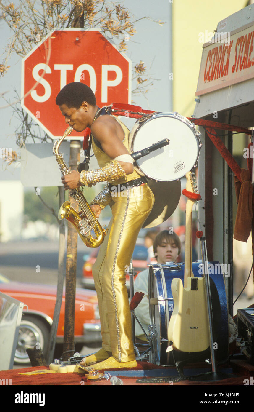 A one man band in a gold lame costume performing on the street Venice CA - Stock Image