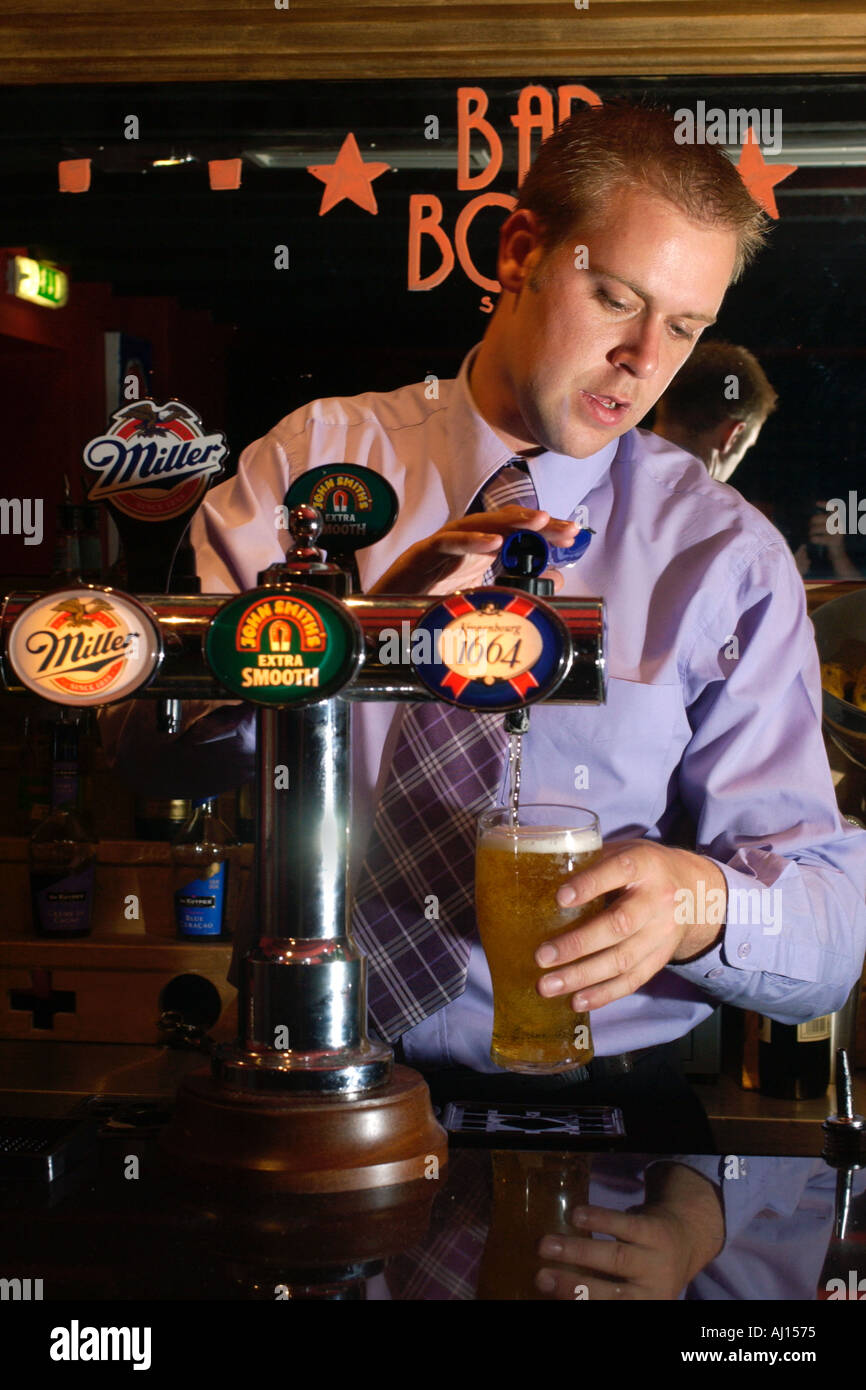 Barman pulling pint of lager at bar in Cardiff South Wales UK - Stock Image