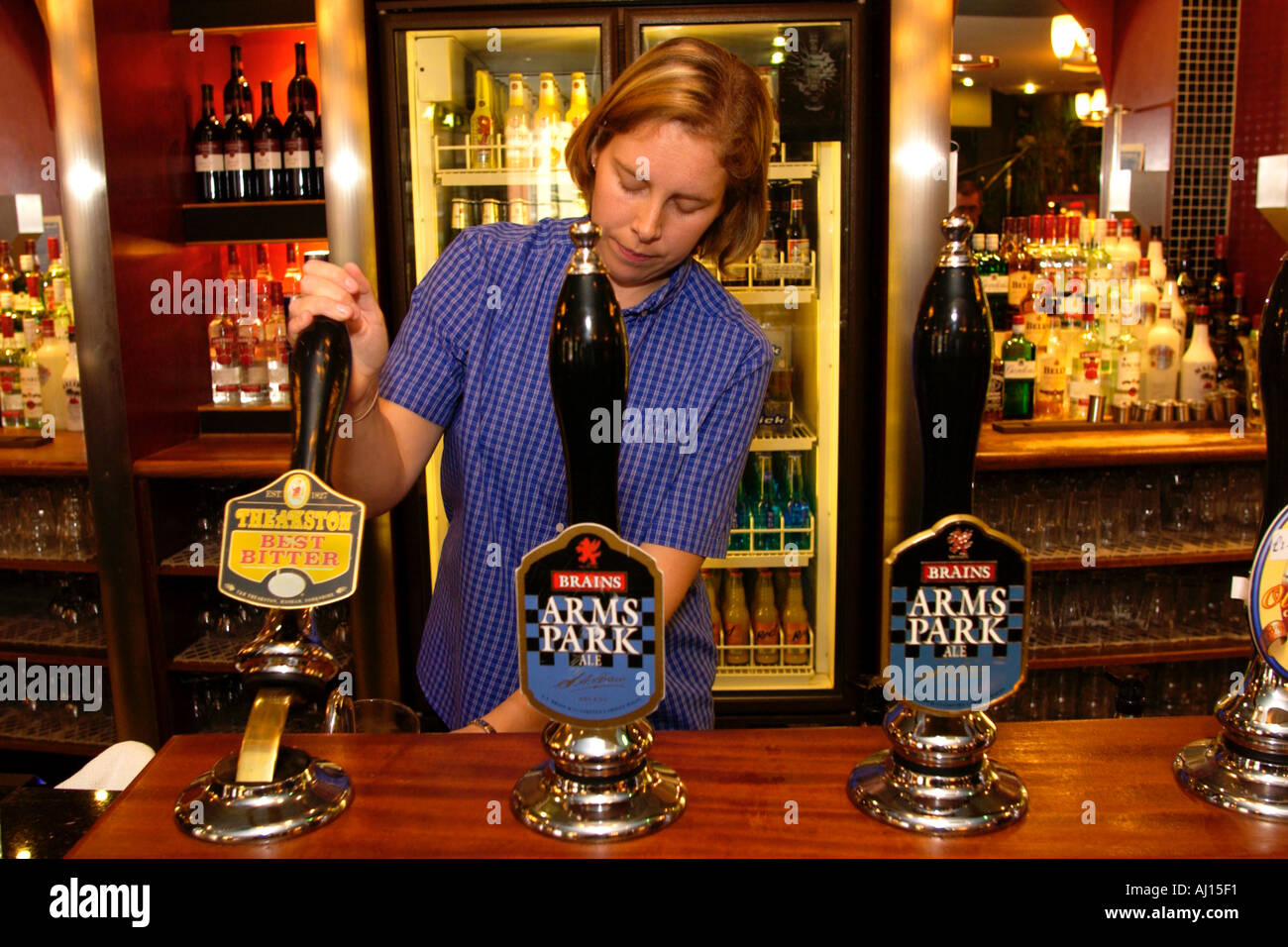 Bar person pulling pints at The Gatekeeper pub in Cardiff South Wales UK - Stock Image