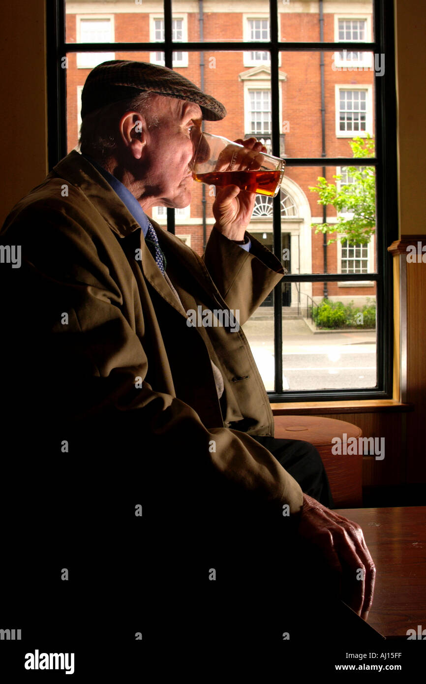Old man drinking pint of beer in pub UK - Stock Image