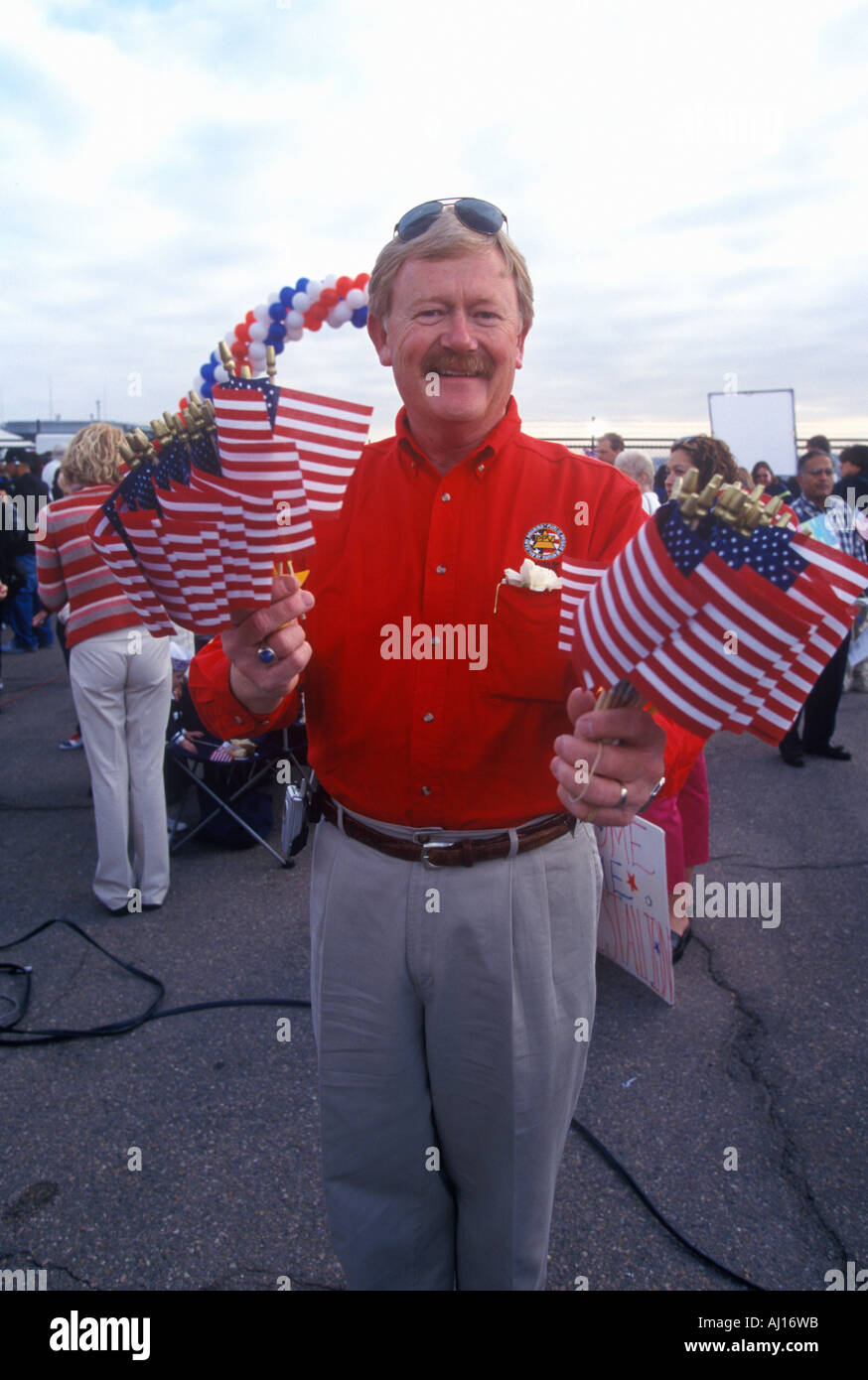 Smiling man with US Flags welcomes home sailors on USS Abraham Lincoln aircraft carrier from Iraq war - Stock Image