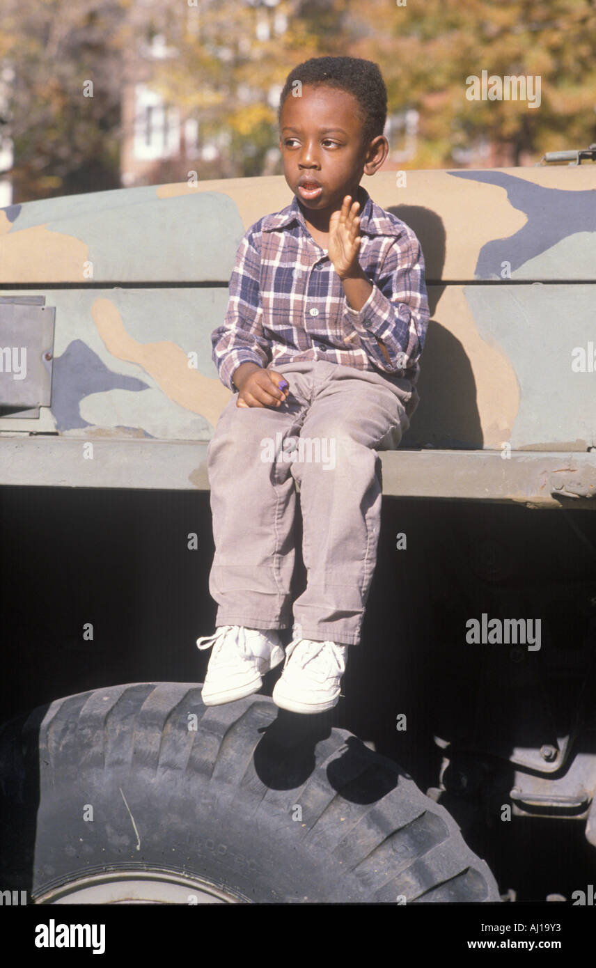 An African American boy sitting on an U S army vehicle - Stock Image