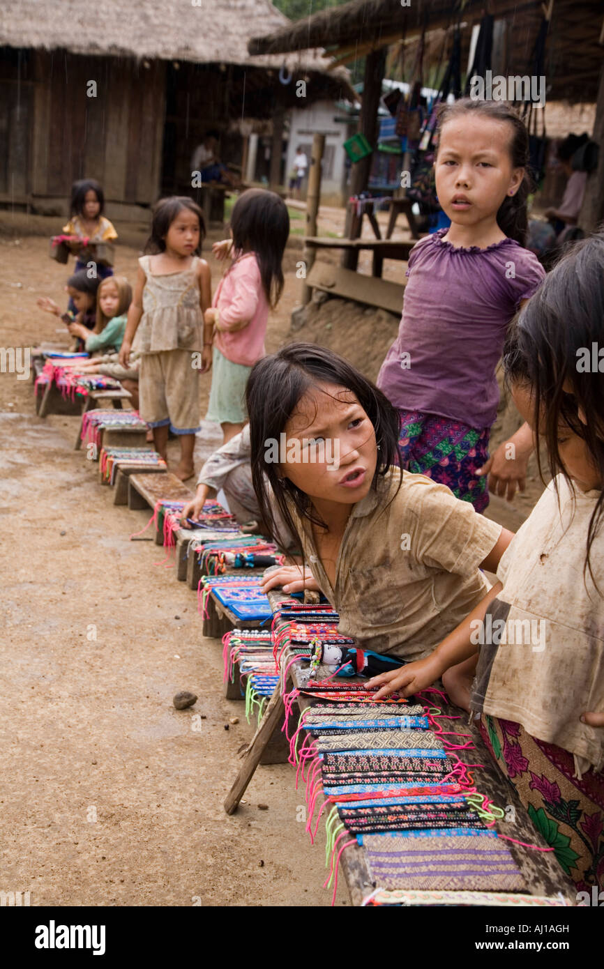 Line of children selling wrist bands to tourists in Hmong tribal village near Luang Prabang Laos - Stock Image