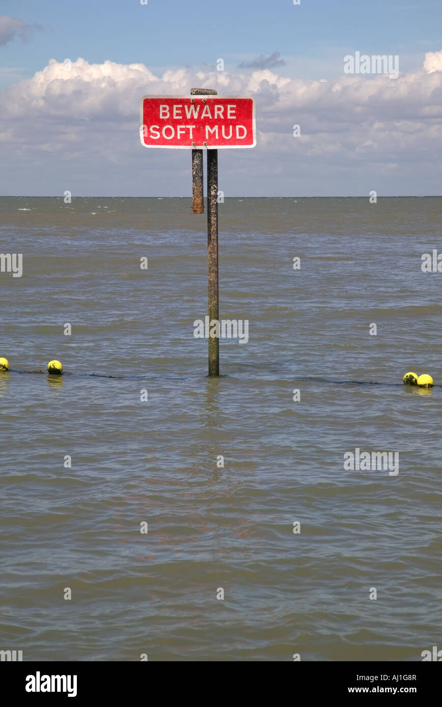 Beware soft mud signpost in the sea - Stock Image