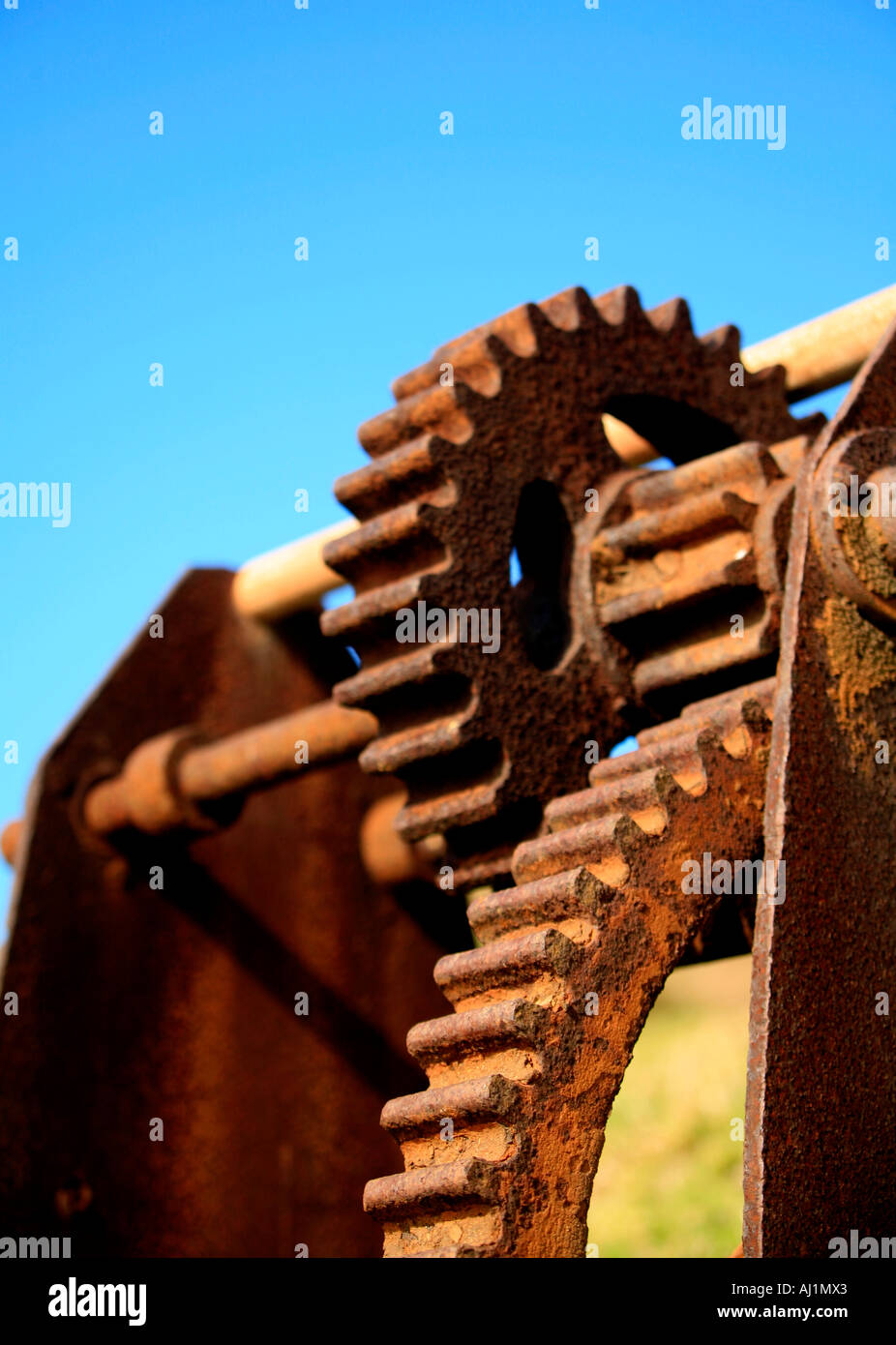 A rusted iron hand winch against a blue sky - Stock Image