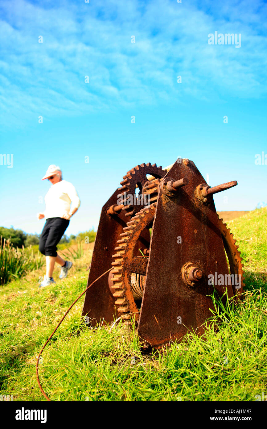 A corroded iron hand winch against a blue sky - Stock Image