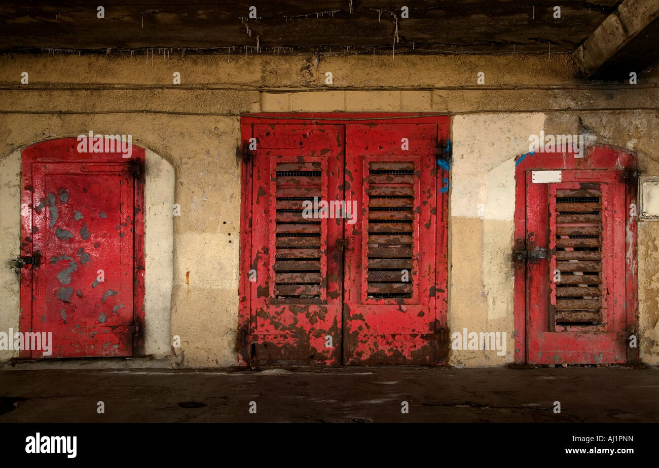 Three rusted old red metal doors in an underground basement - Stock Image