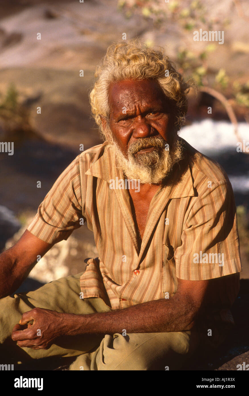 Portrait of aboriginal man, sitting by the river of his homeland.  This is close to where he lives on the Wujal - Stock Image