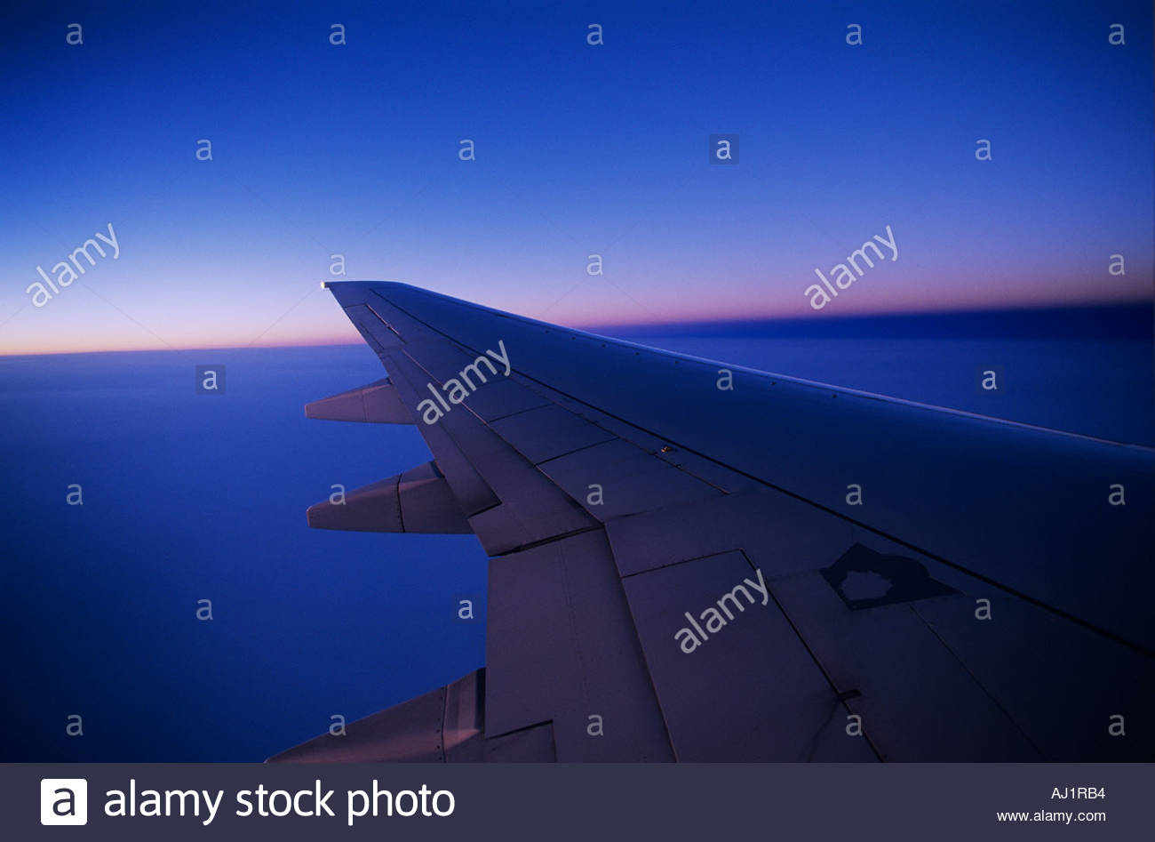 Looking out the window of a commercial Airliner at 35000 feet at Dusk with wing over the USA - Stock Image