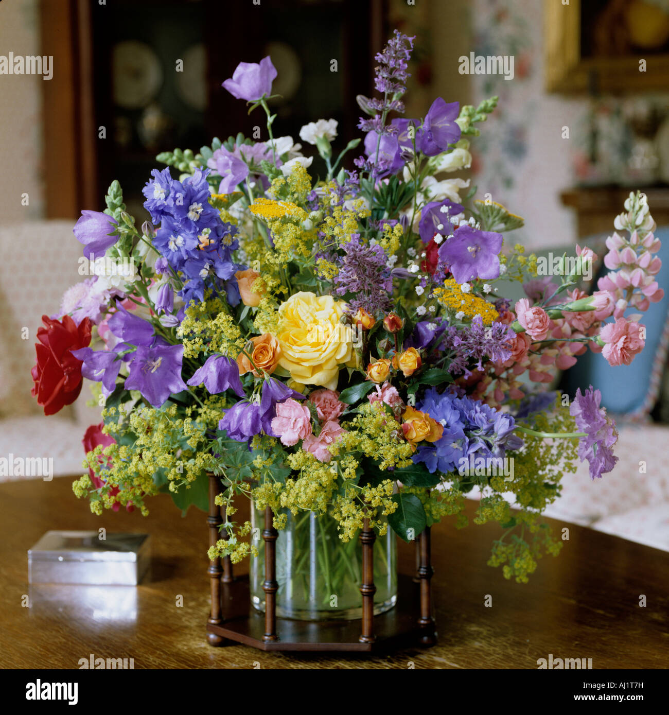 Assorted flower arrangement in glass vase with wooden frame. Stock Photo