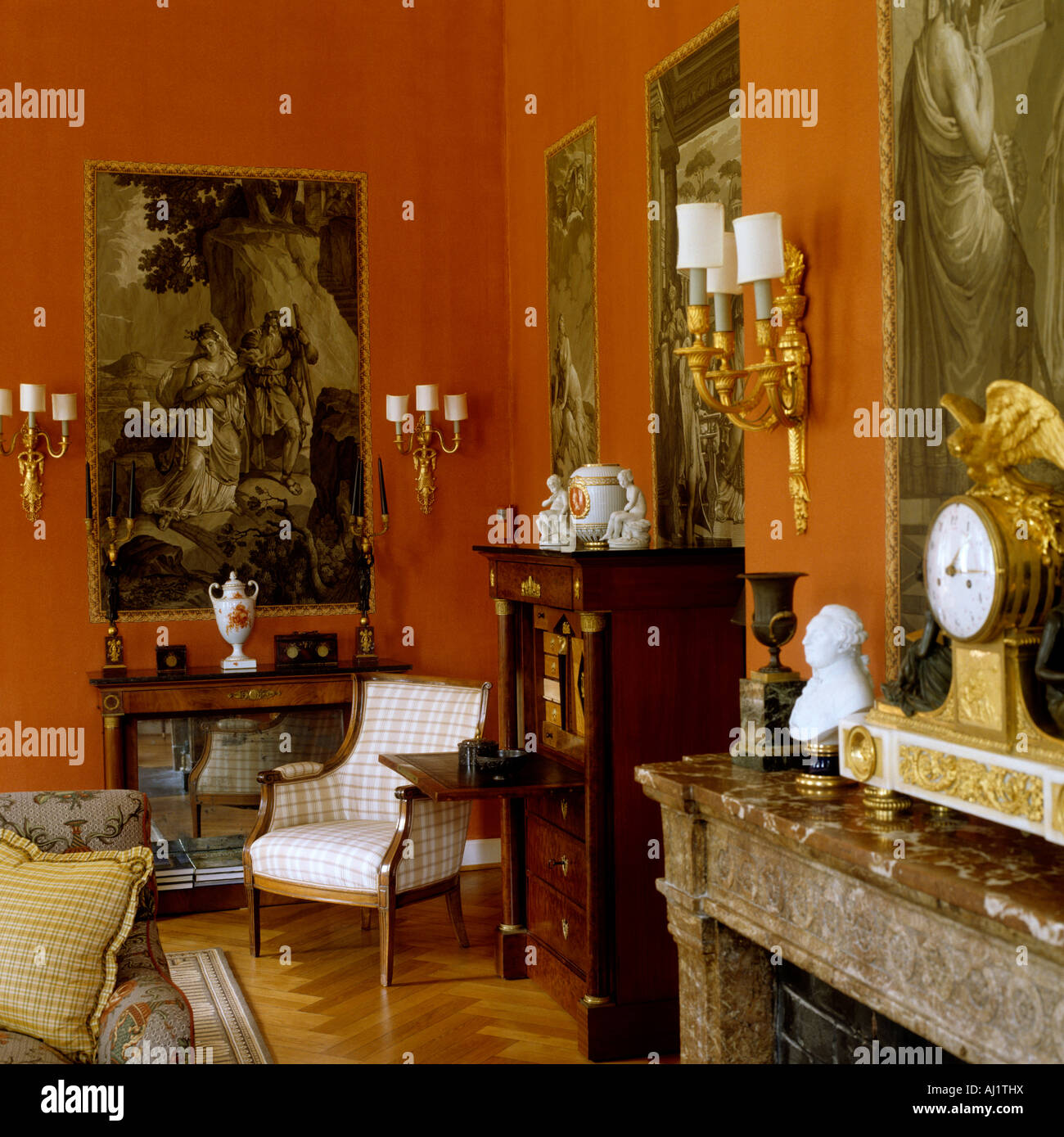 Section of red drawing room with antique furniture and marble mantelpiece  in historic German stately home - Section Of Red Drawing Room With Antique Furniture And Marble Stock