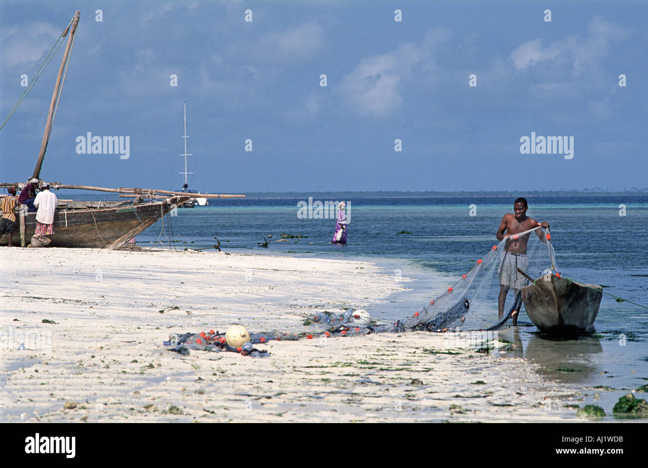 Fisherman tending to his net at the shore at low tide Nungwe Unguja Zanzibar Tanzania East Africa - Stock Image