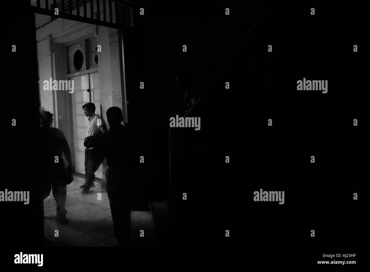 Indonesia Jakarta Reflection of passengers walking through dark interior of Kota Railway Station in downtown - Stock Image