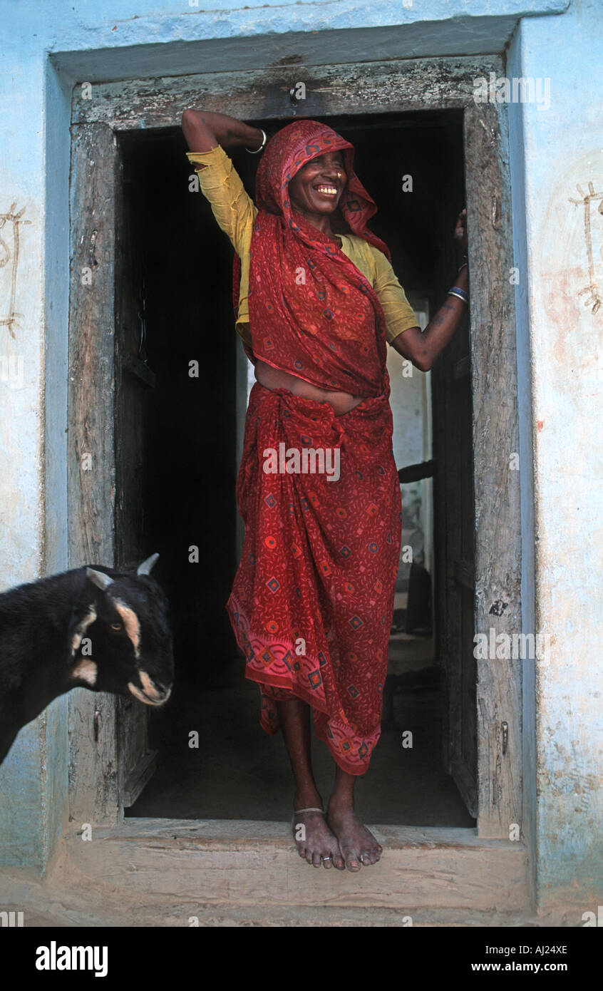 Indian woman standing in the doorway to her rural home A goat enters the frame Madhya Pradesh India - Stock Image