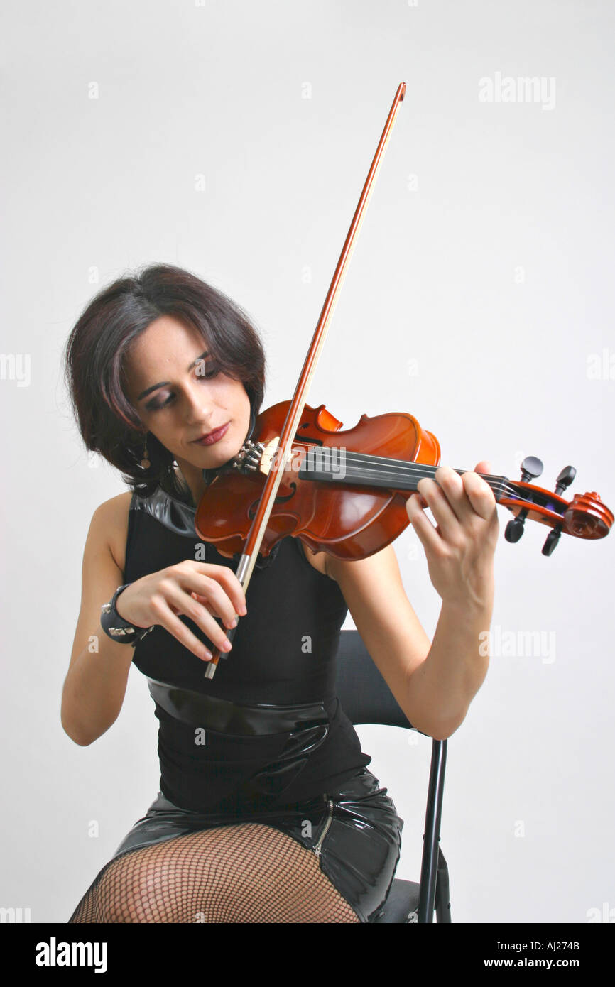 Young woman with heavy rock or punk appearance playing the violin