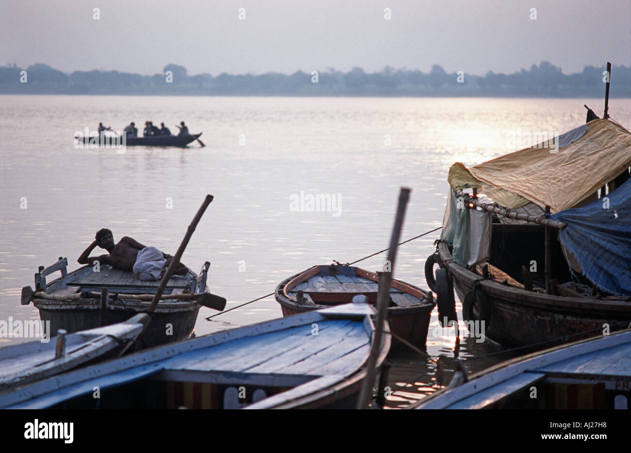 Early morning scene A boatman relaxing on his boat at dawn Silhouetted shapes at dawn The Ganges at Varanasi Uttar Pradesh India - Stock Image