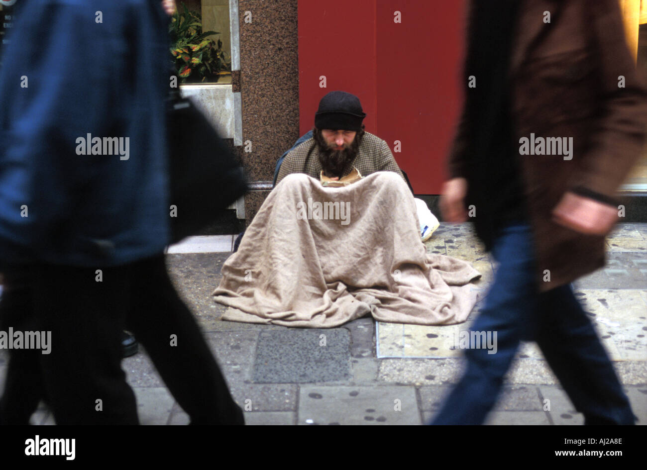 People passing homeless man begging on street, London, England, UK - Stock Image
