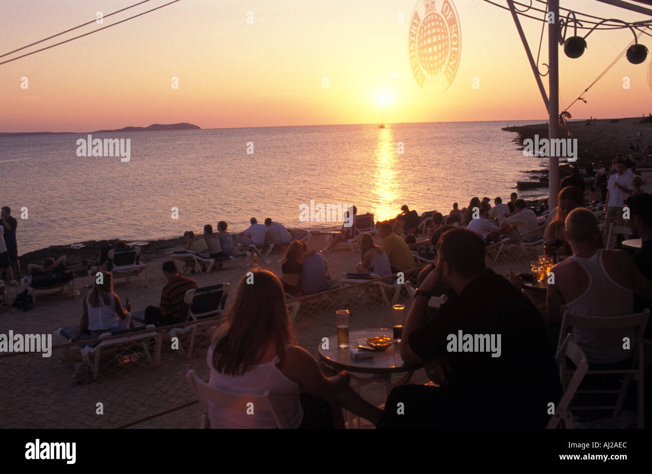 People watching the sun go down on the beach by the Cafe del Mar in San Antonio Ibiza Spain - Stock Image